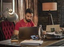 Junger Geschäftsmann, der im dunklen Startstudio sitzt und an Laptop arbeitet Stockbilder