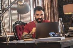 Junger Geschäftsmann, der im gemütlichen Büro auf weichem Stuhl mit Laptop sitzt Stockbilder