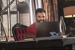 Junger Geschäftsmann, der im gemütlichen dunklen Büro im Stuhl sitzt und Laptop schaut Lizenzfreies Stockfoto