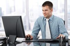 Junger Geschäftsmann, der im modernen Bürolächeln arbeitet Lizenzfreie Stockbilder