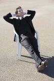 Junger Geschäftsmann, der im Stuhl am Strand sich entspannt Stockbild