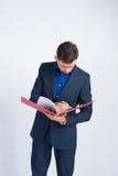 Junger Geschäftsmann, der Informationen in einem Ordner schaut Stockfotografie