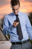 Junger Geschäftsmann, der intelligentes Telefon ta schaut Stockbilder
