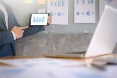 Junger Geschäftsmann in der Klage Datendiagramm auf digitaler Tablette und Dokumente auf der Wand in einem Büro erklärend stockbild