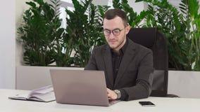 Junger Geschäftsmann in der Klage, die an Laptop arbeitet stock footage