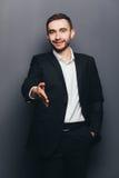 Junger Geschäftsmann in der Klage geben Handerschütterung Lizenzfreie Stockbilder