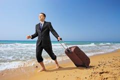 Junger Geschäftsmann in der Klage gehend auf einen Strand mit seinem Gepäck Stockfoto