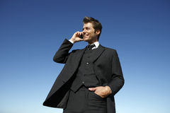 Junger Geschäftsmann in der Klage am Telefon draußen Stockfotos