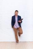 Junger Geschäftsmann, der Kommunikations-Stand des Tablet-Computer-Sozialen Netzes über Wand verwendet Stockfoto