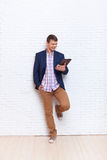 Junger Geschäftsmann, der Kommunikations-Stand des Tablet-Computer-Sozialen Netzes über Wand verwendet Stockbild