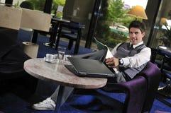 Junger Geschäftsmann, der an Laptop arbeitet Stockbild