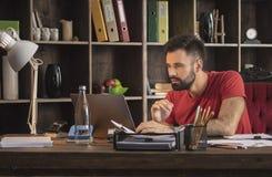 Junger Geschäftsmann, der an Laptop und gefundener interessanter Idee arbeitet Stockfotos