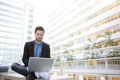Junger Geschäftsmann, der Laptop verwendet lizenzfreie stockfotografie