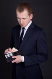 Junger Geschäftsmann, der ledernen Geldbeutel mit Eurobanknoten hält Stockbild