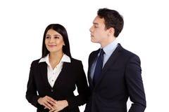Junger Geschäftsmann, der in missbilligender Weise eine Geschäftsfrau betrachtet Lizenzfreie Stockfotos
