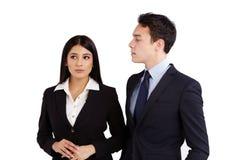 Junger Geschäftsmann, der in missbilligender Weise eine Geschäftsfrau betrachtet Lizenzfreies Stockfoto