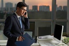 Junger Geschäftsmann, der mit dem Handy vor einem Büro spricht lizenzfreie stockfotografie
