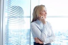 Junger Geschäftsmann, der mit dem Handy vor einem Büro spricht Stockbilder
