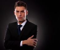 Junger Geschäftsmann, der mit den gefalteten Armen aufwirft Lizenzfreie Stockbilder