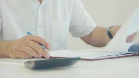 Junger Geschäftsmann, der mit Dokumenten arbeitet und die Blätter durch Stift im Büro unterzeichnet stock footage