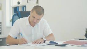 Junger Geschäftsmann, der mit Dokumenten arbeitet und die Blätter durch Stift im Büro unterzeichnet stock video