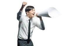 Junger Geschäftsmann, der mit einem Papiermegaphon schreit lizenzfreie stockfotos