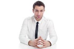 Junger Geschäftsmann, der mit ernstem Gesicht sitzt stockbild