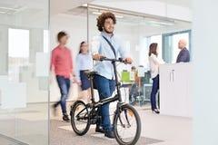Junger Geschäftsmann, der mit Fahrrad während Kollegen im Hintergrund im Büro geht Stockbild