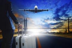 Junger Geschäftsmann, der mit Gepäck auf städtischer Flughafenrollbahn steht Lizenzfreies Stockbild