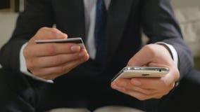 Junger Geschäftsmann, der mit Kreditkarte an einem intelligenten Telefon zahlt stock video footage