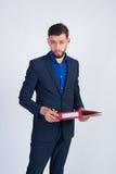Junger Geschäftsmann, der mit rotem Ordner steht Stockfoto