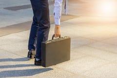 Junger Geschäftsmann, der mit seinem die Rückseite trägt einen Aktenkoffer c steht lizenzfreie stockbilder