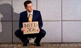 Junger Geschäftsmann, der mit Zeichen Notwendigkeits-Job hockt lizenzfreies stockbild