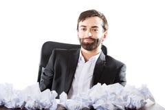 Junger Geschäftsmann, der mit zerquetschten Blättern sitzt Stockfotografie