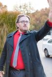 Junger Geschäftsmann, der nach einem Taxi sucht Lizenzfreie Stockfotos