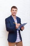 Junger Geschäftsmann, der Ordner-Dokumenten-Schreiben, Geschäftsmann Standing Over Wall hält Lizenzfreie Stockbilder