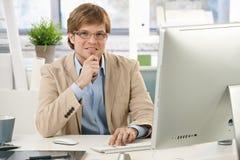 Junger Geschäftsmann, der am Schreibtisch denkt Stockbilder