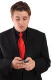 Junger Geschäftsmann in der schwarzen Nachrichtenübermittlung auf Mobiltelefon Stockfoto