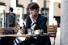Junger Geschäftsmann, der sein Telefon überprüft stockfoto