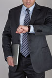 Junger Geschäftsmann, der seine Armbanduhr überprüft die Zeit betrachtet Lizenzfreies Stockbild