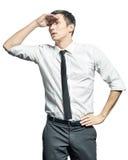 Junger Geschäftsmann, der seine Hand an der Stirn hält und vorwärts schaut stockfotos