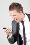 Junger Geschäftsmann, der in seinem Mobiltelefon schreit lizenzfreies stockbild