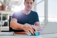 Junger Geschäftsmann, der an seinem Schreibtisch arbeitet Stockbild