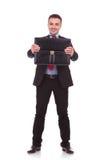 Junger Geschäftsmann, der seinen Aktenkoffer darstellt Stockfotos
