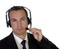 Junger Geschäftsmann, der seinen Kopfhörer justiert Stockfotografie