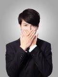 Junger Geschäftsmann, der seinen Mund abdeckt Lizenzfreies Stockfoto