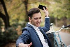 Junger Geschäftsmann, der seinen Smartphone im Park wegwirft lizenzfreie stockbilder