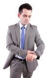 Junger Geschäftsmann, der seins Uhr konsultiert stockfoto