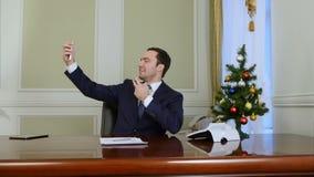 Junger Geschäftsmann, der selfie Foto mit Baum des neuen Jahres unter Verwendung des Mobiltelefons im Büro macht stock video footage