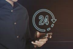 Junger Geschäftsmann, der Smartphone mit 24 Stunden Ikonen-verwendet Stockbild